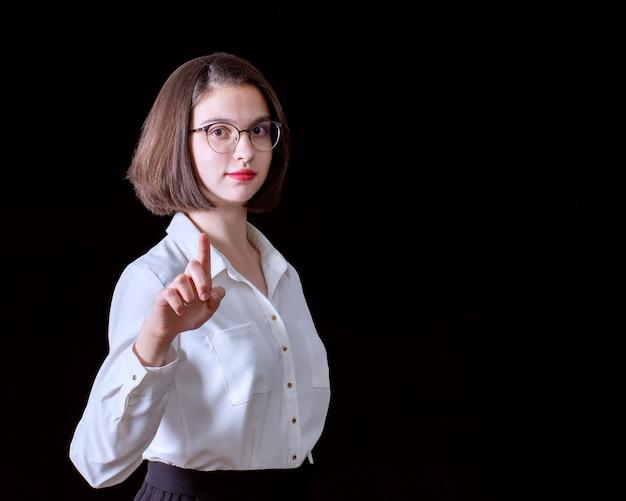 Retrato de uma mulher de negócios jovem bonita apontando um dedo, isolado em um fundo preto. conceito de negócios.