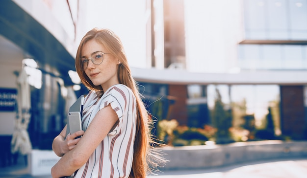 Retrato de uma mulher de negócios jovem bonita segurando um laptop e contra o pôr do sol perto de edifícios comerciais.
