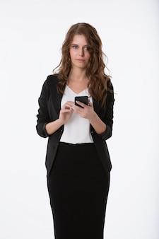 Retrato de uma mulher de negócios jovem linda com um telefone nas mãos