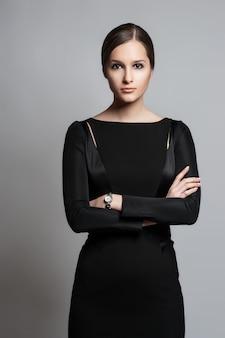 Retrato de uma mulher de negócios jovem sexy em um vestido preto sobre um fundo escuro