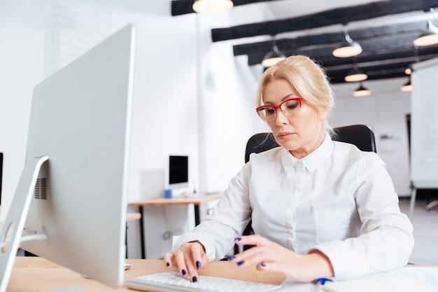Retrato de uma mulher de negócios madura séria trabalhando no escritório com o computador