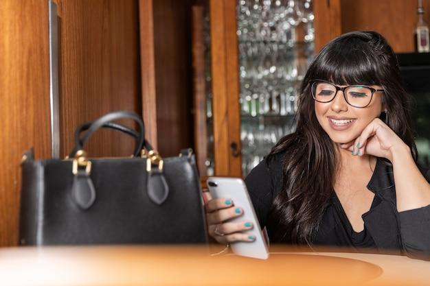 Retrato de uma mulher de negócios nova atrativa que texting uma mensagem em seu smatphone na barra de café.