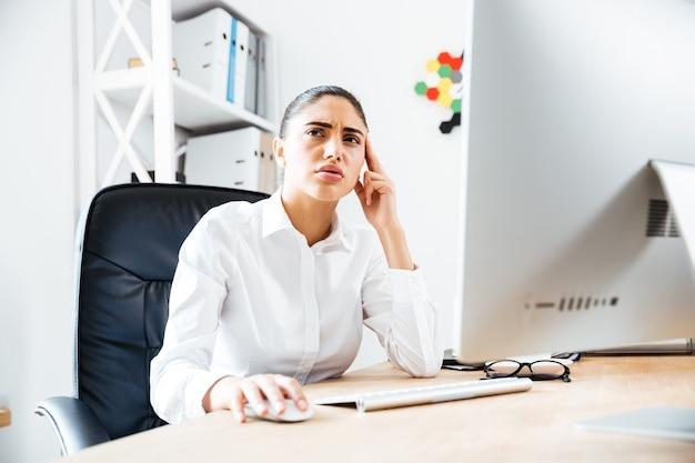 Retrato de uma mulher de negócios pensativa, sentada à mesa no escritório e olhando para longe