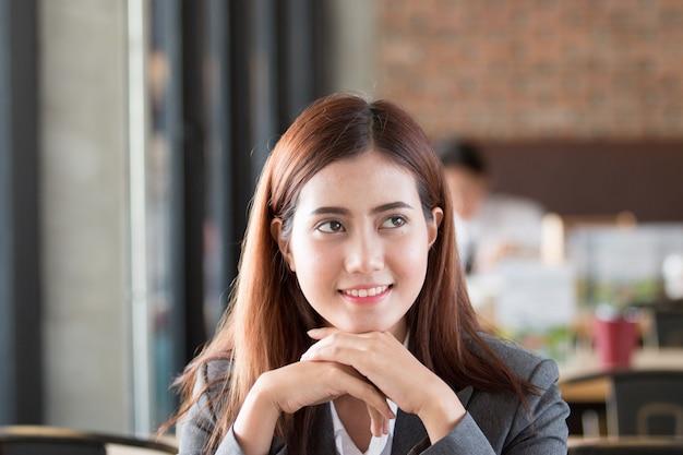 Retrato de uma mulher de negócios profissional do conselheiro de investimento que senta-se na frente do portátil.