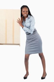 Retrato de uma mulher de negócios que empurra um painel
