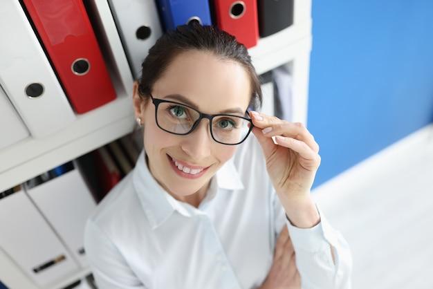 Retrato de uma mulher de negócios sorridente com óculos ao lado do guarda-roupa com pacotes