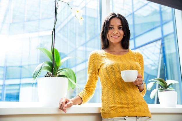 Retrato de uma mulher de negócios sorridente em pé com uma xícara de café no escritório