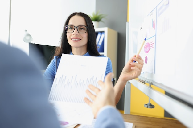 Retrato de uma mulher de negócios sorridente realiza consultoria de negócios para colegas pequenos e