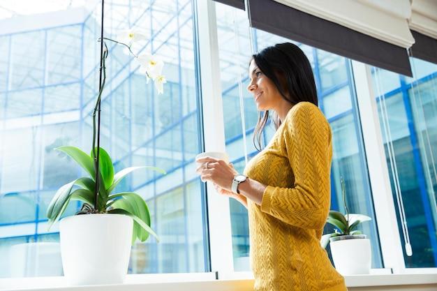 Retrato de uma mulher de negócios sorridente segurando uma xícara com café e olhando para a janela no escritório