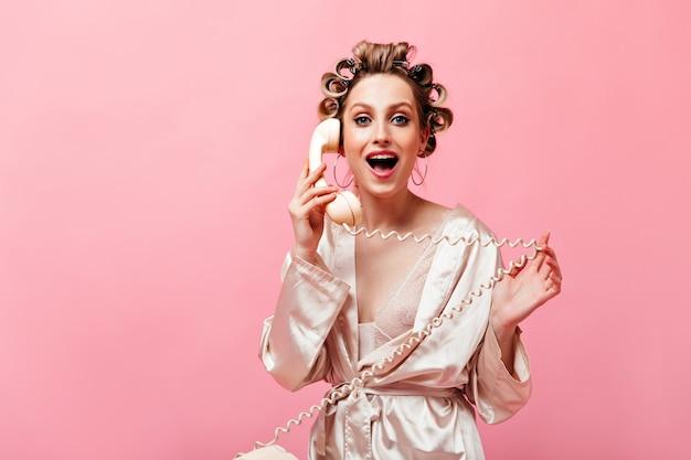 Retrato de uma mulher de olhos azuis com rolinhos de cabelo olhando para frente, falando ao telefone e enrolando provocantemente o fio no dedo