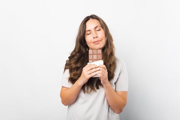 Retrato de uma mulher de olhos fechados apreciando o cheiro de chocolate.