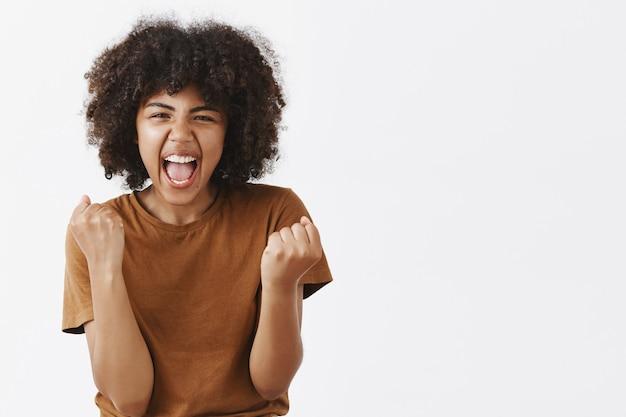 Retrato de uma mulher de pele escura, alegre, animada e emotiva, torcendo pelo time favorito, gritando de empolgação e alegria cerrando os punhos em gesto de vitória ou triunfo