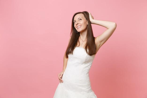 Retrato de uma mulher delicada em um vestido branco em pé, sonhando, olhando para cima, mantendo a mão perto da cabeça