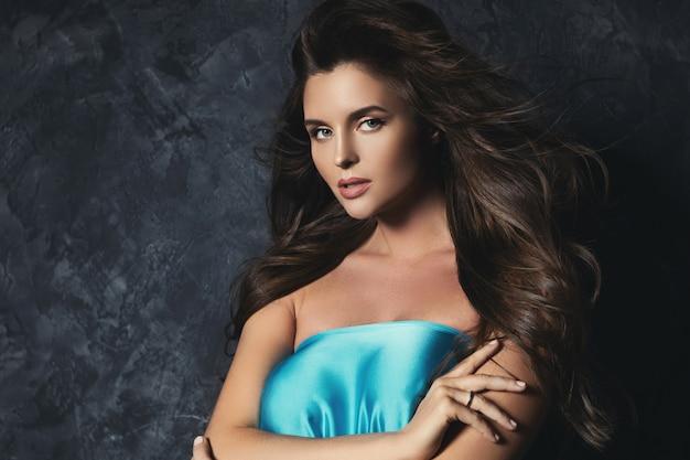 Retrato de uma mulher deslumbrante com um lindo cabelo encaracolado e maquiagem profissional