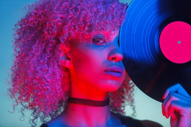 Retrato de uma mulher discoteca segurando um vinil com música dos anos oitenta e luz de neon