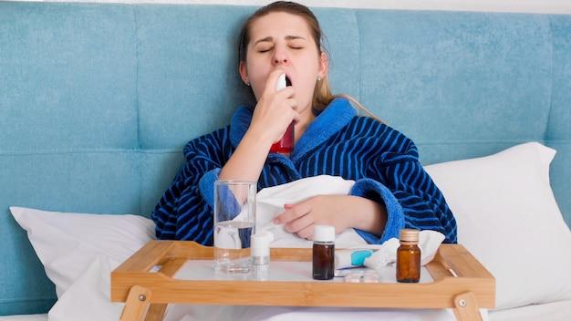Retrato de uma mulher doente, deitada na cama e usando spray para a garganta.