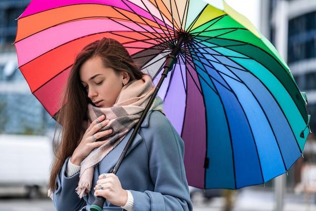 Retrato de uma mulher doente triste e infeliz no outono roupas quentes com guarda-chuva durante o tempo chuvoso no outono. temporada de gripes e resfriados. proteção contra chuva
