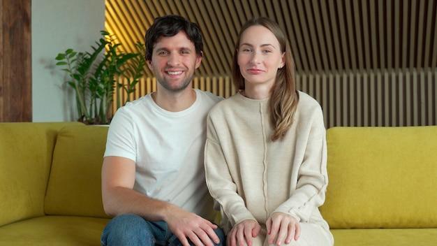 Retrato de uma mulher e um marido acenando com as mãos, olhando para a câmera e dizendo olá, sentado no sofá da sala