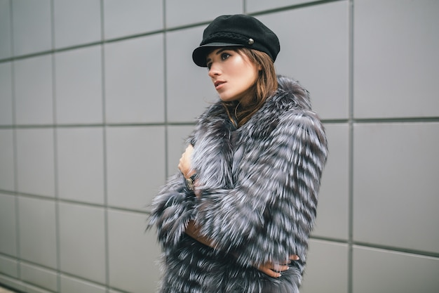 Retrato de uma mulher elegante caminhando pela cidade com um casaco de pele quente, inverno, clima frio, usando boné preto, tendência da moda de rua