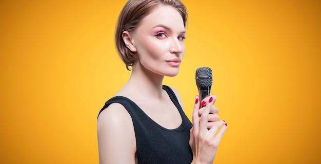 Retrato de uma mulher elegante e elegante com um microfone. fundo amarelo. conceito de karaokê. mídia mista