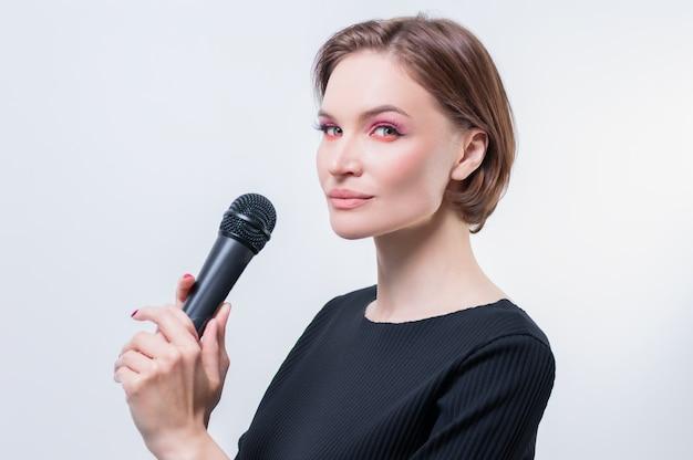 Retrato de uma mulher elegante e elegante com um microfone. fundo branco. conceito de karaokê. mídia mista