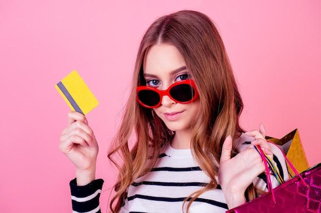 Retrato de uma mulher elegante e jovem atraente em um suéter listrado e óculos de sol vermelhos contém muitas sacolas de compras e cartão de crédito em um fundo rosa no estúdio. conceito de vício em compras e venda