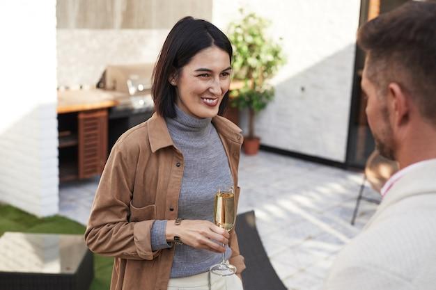 Retrato de uma mulher elegante e moderna sorrindo alegremente enquanto conversava com um amigo em uma festa ao ar livre,