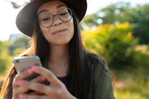 Retrato de uma mulher elegante e satisfeita usando chapéu e óculos, usando o celular, enquanto caminhava no parque verde em um dia ensolarado