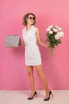Retrato de uma mulher elegante em um elegante vestido listrado branco segurando uma bolsa e um buquê de flores