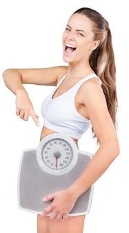 Retrato de uma mulher em forma apontando para uma balança de peso