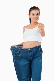 Retrato de uma mulher em forma de jeans muito grande com o polegar para cima