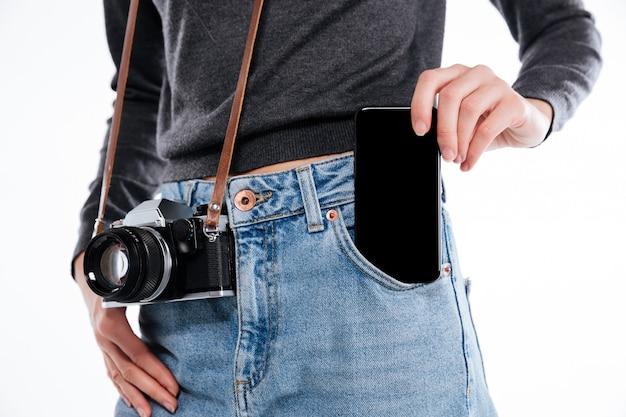Retrato de uma mulher em jeans com câmera retro