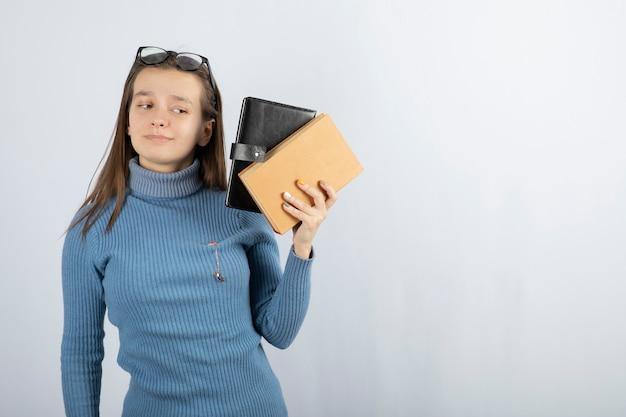 Retrato de uma mulher em óculos segurando dois livros sobre fundo branco acinzentado.
