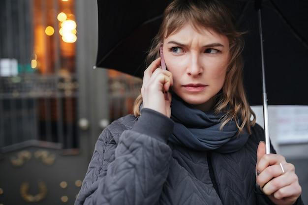 Retrato de uma mulher em pé na rua com um guarda-chuva preto falando ao celular, olhando seriamente para o lado