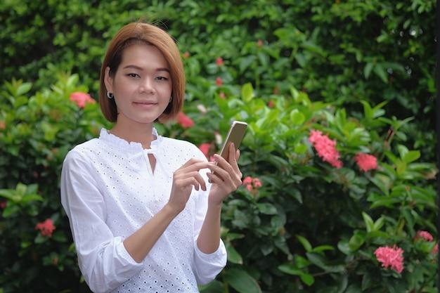 Retrato de uma mulher em pé segurando um smartphone no exterior verde