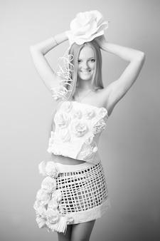 Retrato de uma mulher em um vestido de papel com flores sobre fundo cinza. fotografia a preto e branco