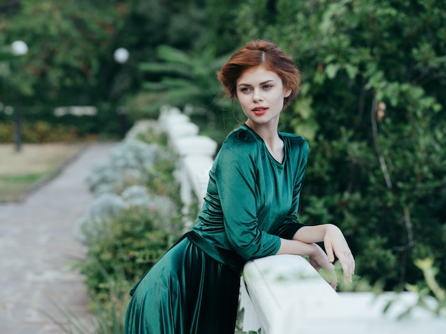 Retrato de uma mulher em um vestido verde arquitetura ar fresco folhas verdes.
