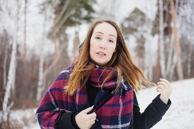 Retrato de uma mulher em uma floresta de inverno, roupas quentes, cachecol