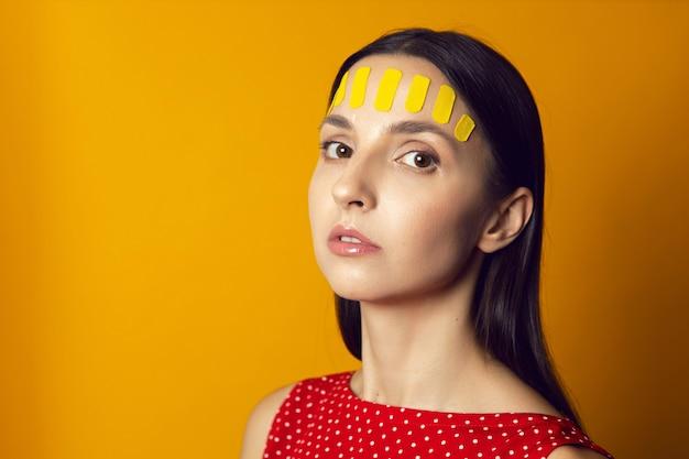 Retrato de uma mulher em uma parede amarela com uma fita cinesiota do rosto na testa