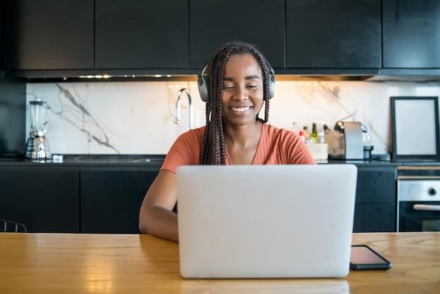 Retrato de uma mulher em uma videochamada com laptop enquanto trabalhava em casa.