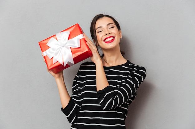 Retrato de uma mulher encantada, segurando a caixa de presente