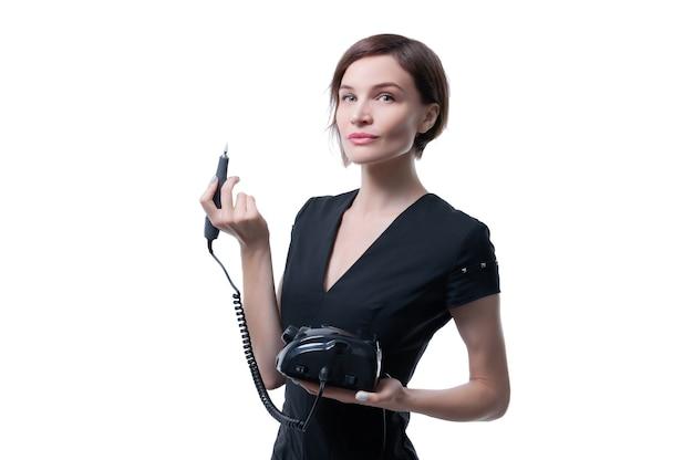 Retrato de uma mulher encantadora com um aparelho de manicure