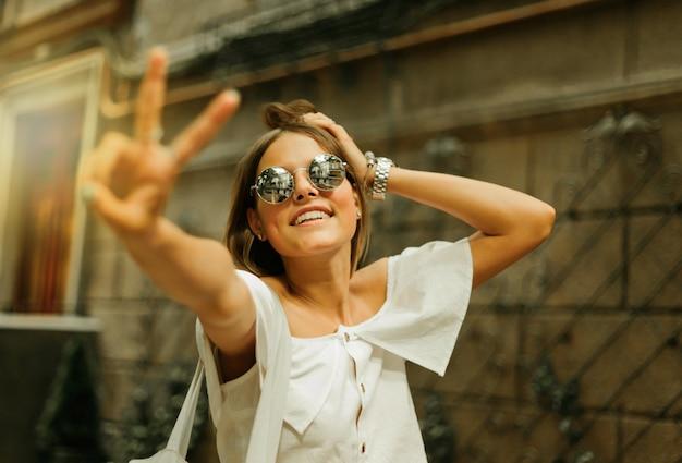 Retrato de uma mulher encantadora e alegre em roupas da moda e óculos escuros