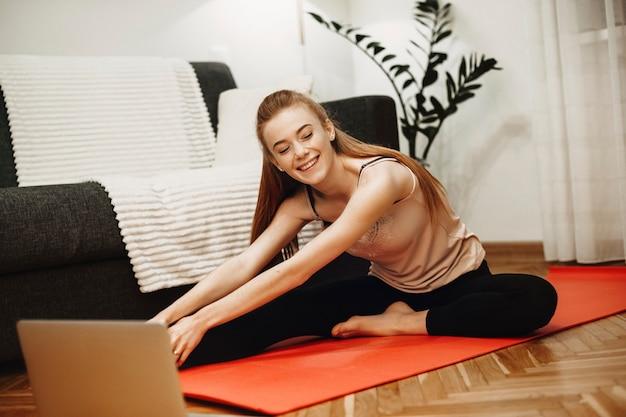 Retrato de uma mulher encantadora, fazendo exercícios de alongamento em casa, olhando vídeos instrutivos em seu laptop no chão.