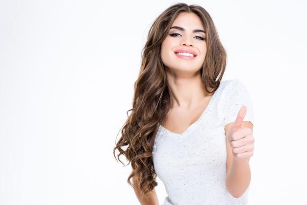 Retrato de uma mulher encantadora feliz aparecendo o polegar isolado em uma parede branca
