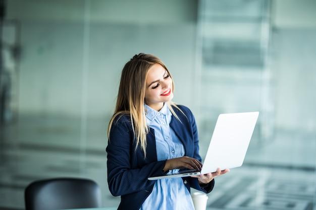 Retrato de uma mulher encantadora, simpática e positiva com óculos na cabeça, tendo o laptop nas mãos, olhando de pé no local de trabalho, estação