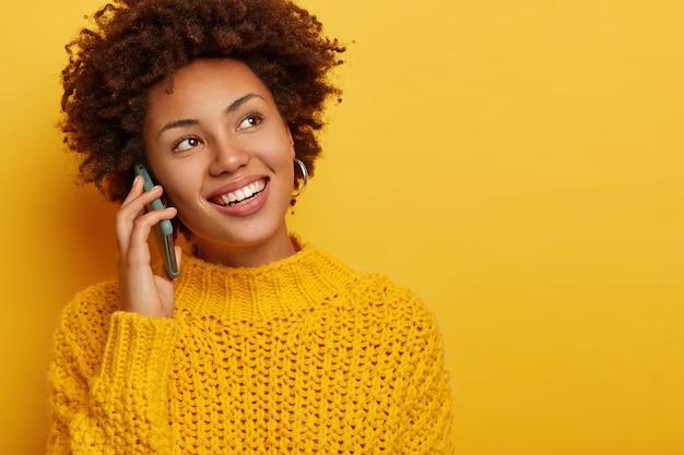 Retrato de uma mulher encaracolada feliz chama um amigo, segura o celular perto da orelha, olha para o lado com um largo sorriso cheio de dentes, usa um macacão amarelo de malha, espaço em branco