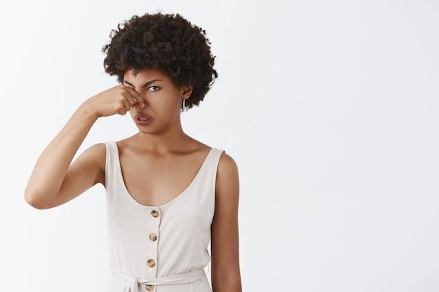 Retrato de uma mulher engraçada afro-americana profundamente desapontada e descontente com um penteado afro cobrindo o nariz com dedos franzidos de antipatia