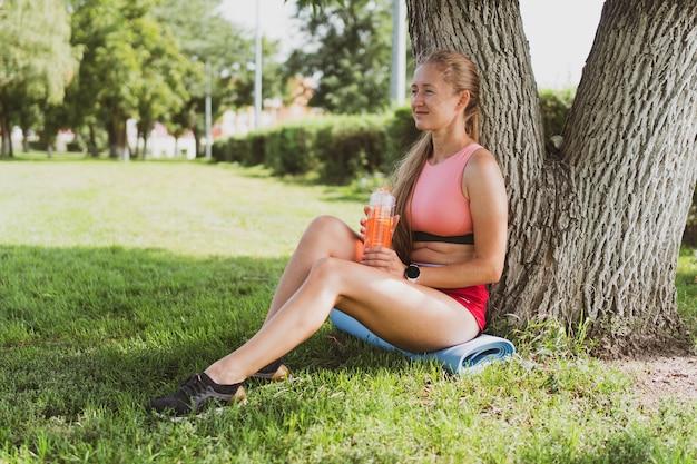 Retrato de uma mulher esportiva com cabelo comprido em roupas esportivas no parque