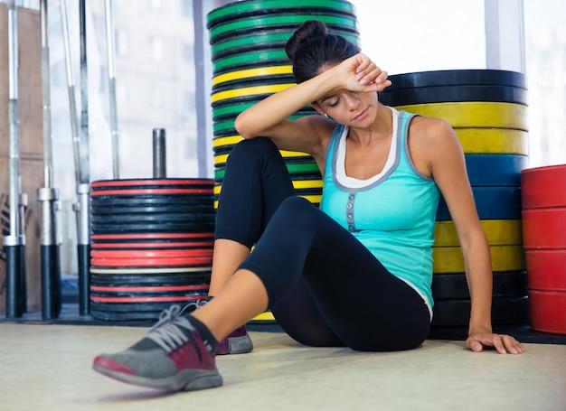 Retrato de uma mulher esportiva descansando no chão em uma academia